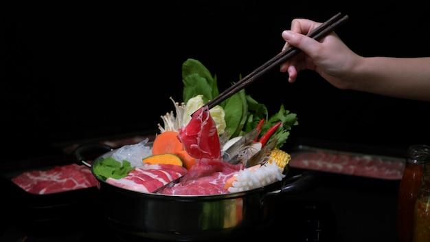新鮮なスライスした肉、魚介類、野菜と黒の背景を持つ鍋でしゃぶしゃぶを食べる女性のショットをトリミング