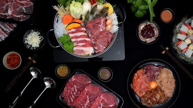 Вид сверху шабу-шабу в горячем горшке, свежее нарезанное мясо, морепродукты, овощи и соус для погружения с черным фоном