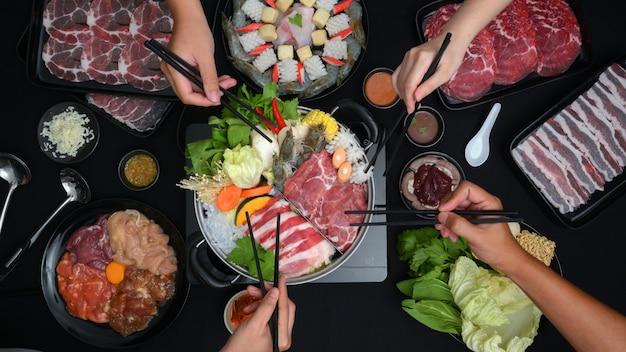 新鮮なスライスした肉、魚介類、黒の背景を持つ野菜と鍋でしゃぶしゃぶを食べる人の平面図