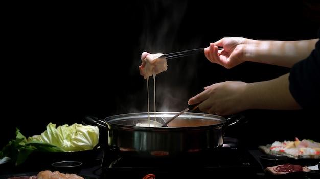 黒の背景を持つチーズに浸した新鮮なスライス肉と鍋でしゃぶしゃぶを食べる女性のショットをトリミング