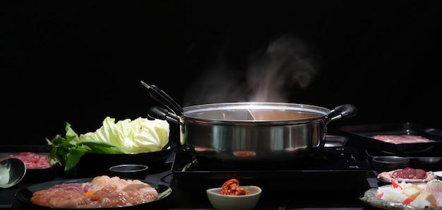 鍋、新鮮な肉、魚介類、黒の背景を持つ野菜のしゃぶしゃぶのセット