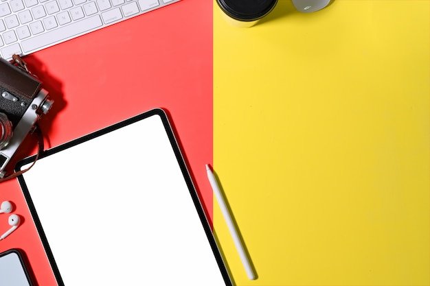 オフィスのカラフルなデスク作業スペースとモックアップタブレット