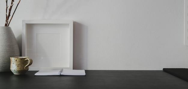 Крупным планом вид модного рабочего места с копией пространства и макет кадра на черном столе и белой стене