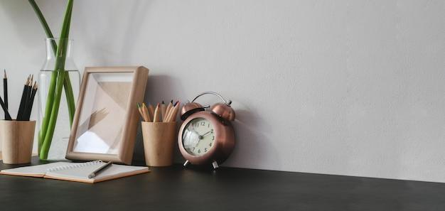 事務用品と黒いテーブルにコピースペースを持つトレンディな職場のショットをトリミング