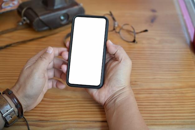 木製のワークスペースの机の上にモバイルのスマートフォンを使用してトップビュー男