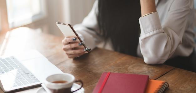 快適なオフィスルームで彼女のプロジェクトに取り組んでいる間スマートフォンを使用して実業家のショットをトリミング