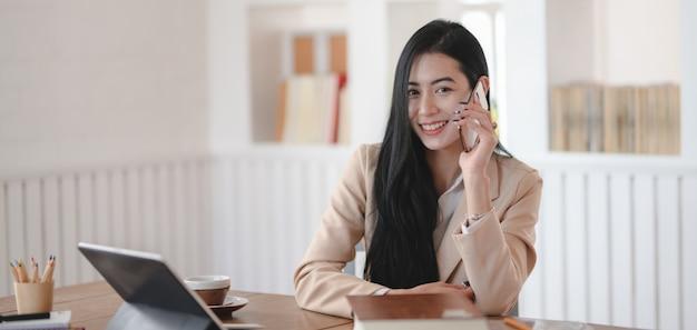 Портрет молодой коммерсантки говоря на телефоне с клиентом пока усмехающся к камере