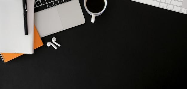 黒いテーブルにラップトップコンピューターとオフィス用品と暗いトレンディな職場のオーバーヘッドショット