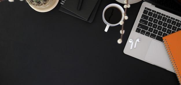 ラップトップコンピューター事務用品と黒いテーブルのコピースペースとトレンディな事務室のオーバーヘッドショット