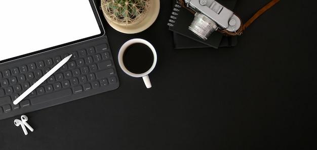 Вид сверху модного фотографа на рабочем месте с макет цифрового планшета, камеры и канцелярских принадлежностей на черном столе