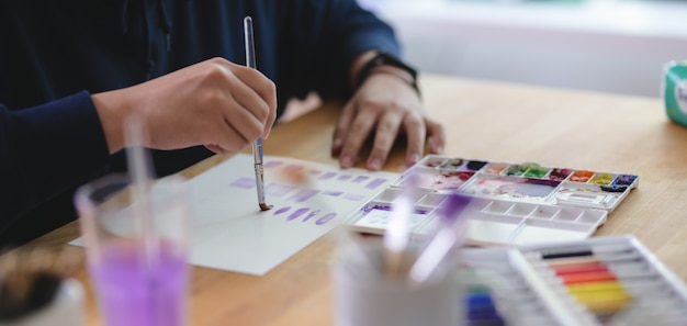 Художник рисует на бумаге для рисования акварелью на удобном рабочем месте