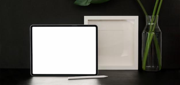 空白の画面のタブレットと黒い壁と黒いテーブル上のフレームのモックアップとトレンディな事務室