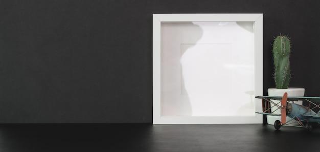 Модный кабинет с макетом кадра и копией пространства на черном столе с черной стеной