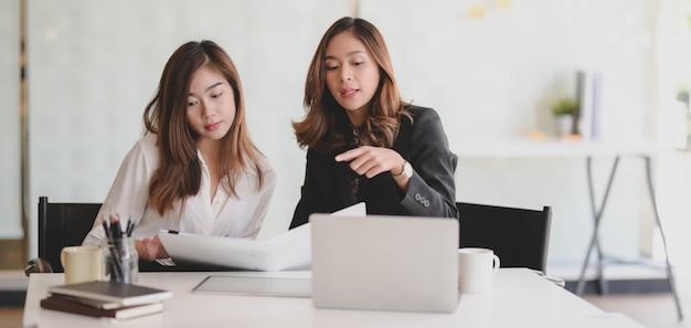 Молодая красивая коммерсантка объясняя ее идеи к ее сотруднику в современном офисе