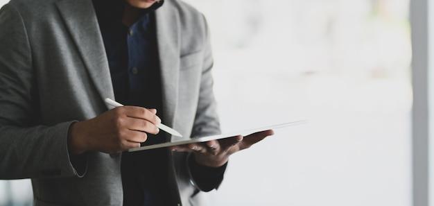 彼のプロジェクトに取り組んでいる間デジタルタブレットを使用するビジネスマン