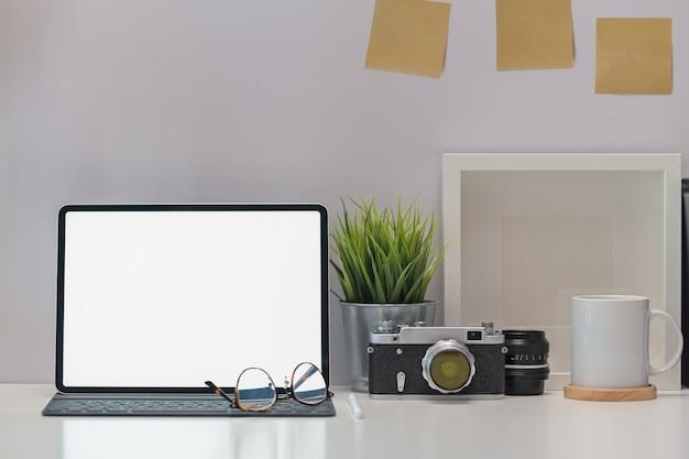 スタイリッシュな職場デスクビンテージカメラ、空白の画面のタブレットとガジェット