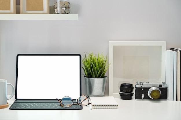 空白の画面のタブレット、ポスター、書籍、ワークスペース上のビンテージカメラのモックアップ