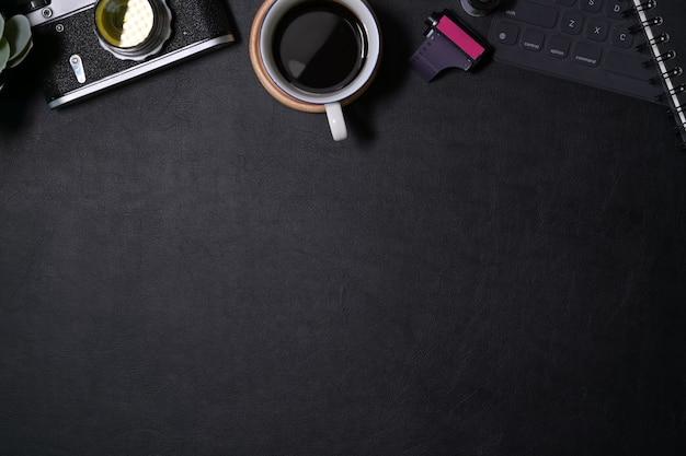ビンテージカメラ、フィルム、コーヒー、コピースペースを備えたオフィスレザーダークデスク
