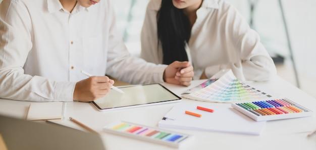 近代的なオフィスで一緒に彼らのコンセプトに取り組んでいる若いグラフィックデザイナーチーム
