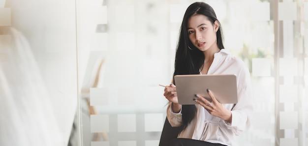 タブレットで彼女のプロジェクトに取り組んでいると、近代的なオフィスに立っている間カメラを見て若い美しいグラフィックデザイナーの肖像画