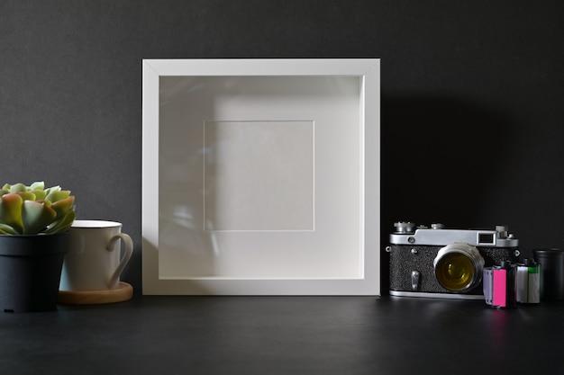 ダークレザーの机の上のビンテージフィルムカメラとモックアップポスターフォトフレーム