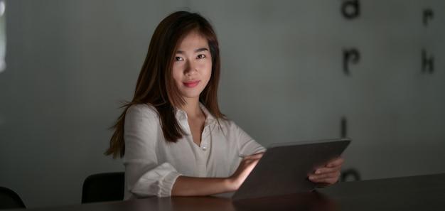Молодая трудолюбивая азиатская коммерсантка работая над ее проектом пока использующ таблетку в современной комнате офиса на ноче