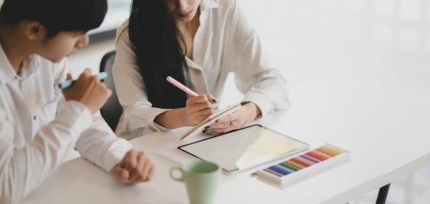 現代のオフィスでタブレットと一緒に彼らのプロジェクトに取り組んでいる若いプロのグラフィックデザイナー