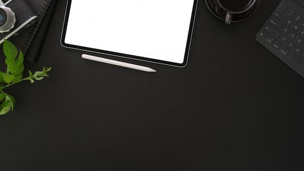 Вид сверху темного стильного рабочего места с макетом планшета и канцелярских принадлежностей на темном столе