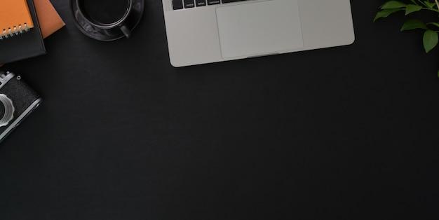 黒いテーブルにラップトップコンピューターとオフィス用品と暗いスタイリッシュな職場のオーバーヘッドショット