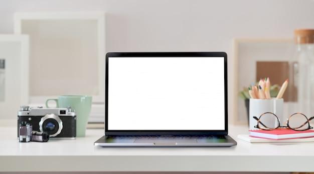 空白の画面のノートパソコン、ビンテージカメラ、ホームオフィス用品とロフトのワークスペース