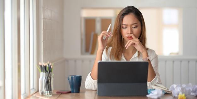 Молодая красивая коммерсантка сконцентрировала в ее работе пока использующ цифровую таблетку в комнате офиса