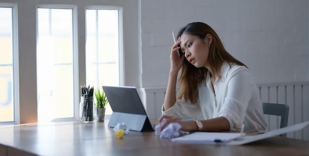 Утомленная красивая азиатская бизнес-леди работая с головной болью в комнате офиса