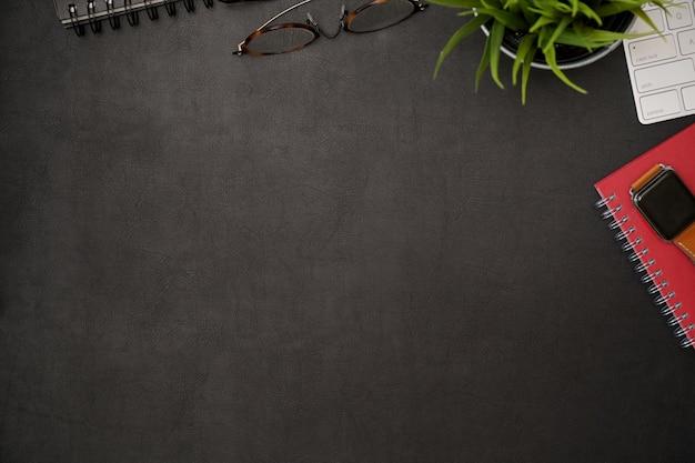 Темный кожаный офисный стол с гаджетом для домашнего офиса и копией пространства