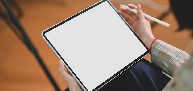 空白の画面デジタルタブレットを使用しながら彼女のプロジェクトに取り組んでいる実業家