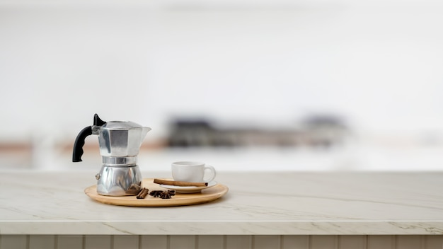 Крупным планом вид макет горшок и чашка кофе на мраморном столе с размытой кухней