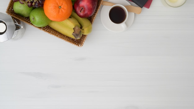 Вид сверху таблицы в гостиной с копией пространства, корзина с фруктами, чашка кофе и горшок мока на белом деревянном столе