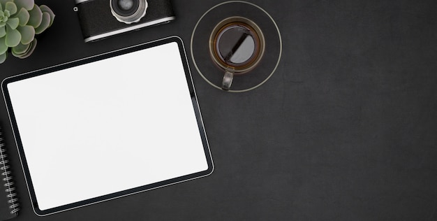 空白の画面タブレットと黒い机の上の黒いコーヒーカップと暗いモダンな職場の平面図