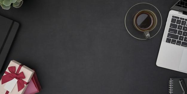 事務用品と黒いテーブルのコピースペースと暗いモダンな職場の平面図
