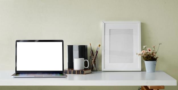 Обрезанный снимок открытого ноутбука с пустым экраном, канцелярских принадлежностей и рамки