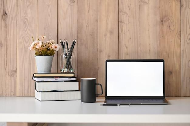 空白の画面のノートパソコン、花、本、コーヒーのマグカップと職場の白いテーブル