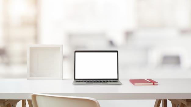 Крупным планом вид рабочей области с открытым пустым экраном ноутбука, рама и блокнот на белом столе с размытым кабинет