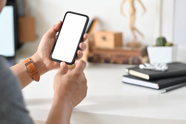 デスクのワークスペースでモバイルのスマートフォンを使用してクローズアップ男性の手