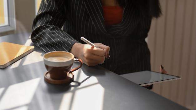 Обрезанный снимок женского фрилансера, работающих на цифровой планшет, сидя в кафе