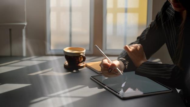 Взгляд со стороны женского фрилансера работая на цифровой таблетке пока сидящ в кофейне