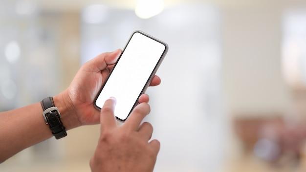 空白の画面のスマートフォンを使用して実業家のクローズアップビュー