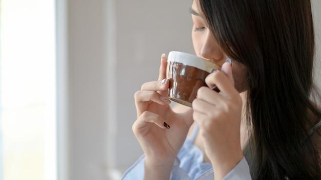 リビングルームに立っている間朝のコーヒーを飲む女性のショットのトリミング
