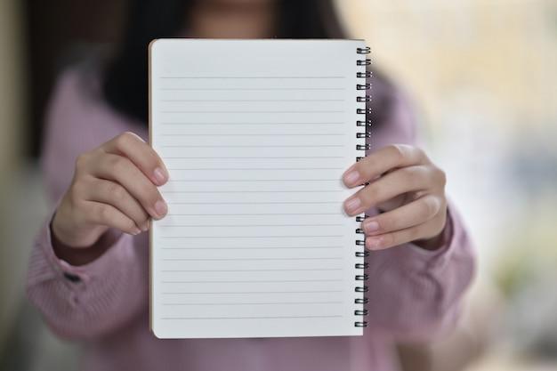 Обрезанный снимок молодой девушки, показывая пустой белый блокнот в руках