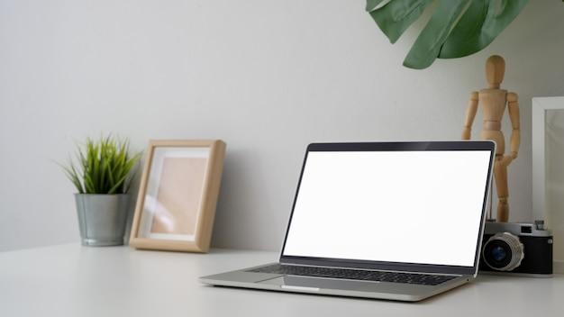 Обрезанный снимок рабочего места с пустым экраном ноутбука, камеры и украшения