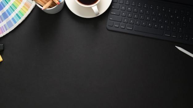 黒いテーブルにワイヤレスキーボード、ペイントツール、コーヒーカップのある職場のトップビュー