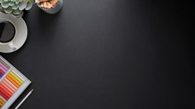 コピースペース、ペイントツール、黒いテーブルの上のコーヒーカップと職場のオーバーヘッドショット